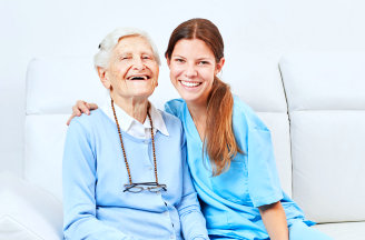 caregiver and her old woman patient smiling at camera