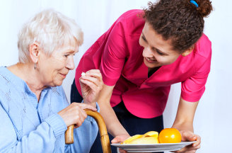 caregiver giving food to her patient