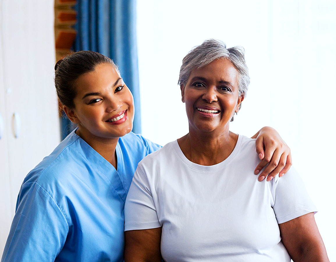 caregiver and her old woman patient looking each other while smiling