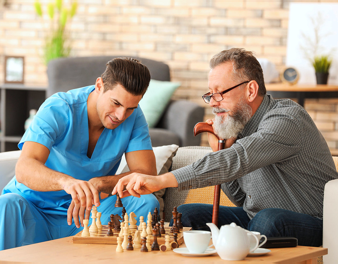 caregiver and his old patient playing chess