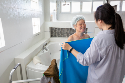 caregiver giving a clean towel to senior woman