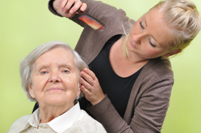 caregiver combing the hair of senior woman