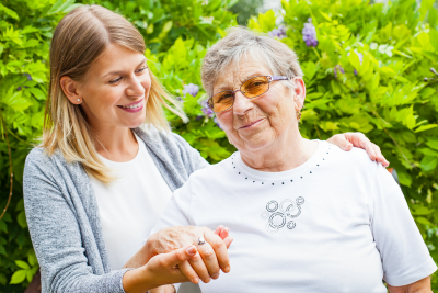caregiver and senior woman wearing eyeglasses are smiling