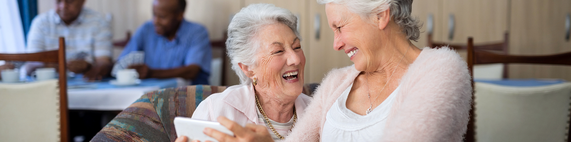 old women looking at each other while smiling""